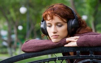 young pensive woman with headphones on trying to make a life-changing decision