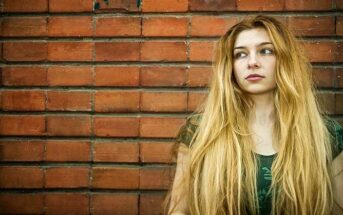 young unsatisfied woman standing in front of a brick wall