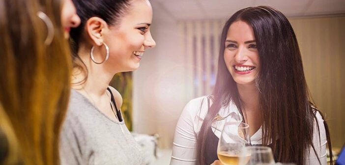 young woman being more outgoing and striking a conversation with two other women