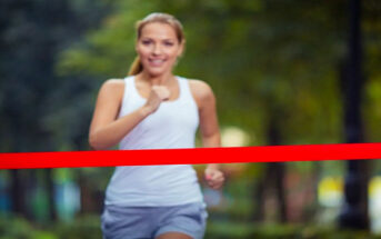 young woman running toward finish line - illustrating finishing what you started