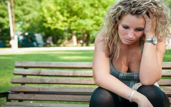 young woman sitting on a bench struggling with a bad memory and wishing she could forget it