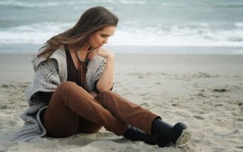 worried young woman sitting on a beach wondering how to fix her life