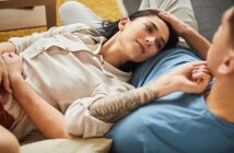 serial monogamist woman lying with head on lap of her boyfriend