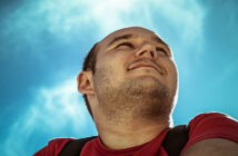 photo looking up at man against backdrop of a blue sky