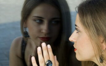 young woman looking at her reflection in a window, asking what kind of person she wants to be