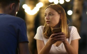 a young woman looking at her phone on a bad date - she hates dating