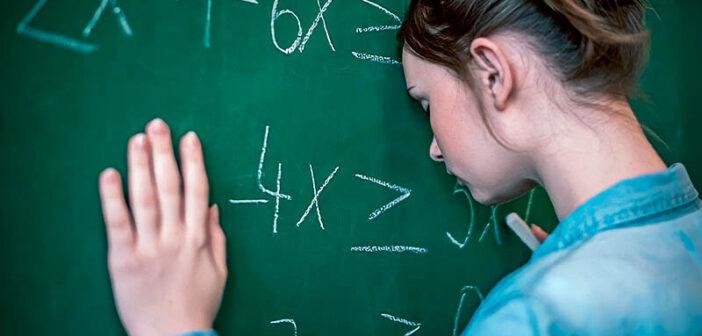 teenage girl with head against blackboard feeling dumb because of school