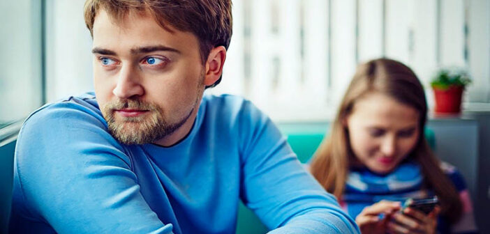 man looking off with girlfriend in the background