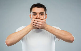 man with hands over his mouth illustrating not interrupting people