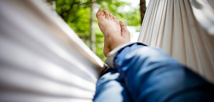 view of a person's legs and feet in a hammock - illustrating how to relax