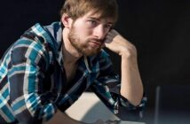 young man who looks bored and lonely thinking he has no life