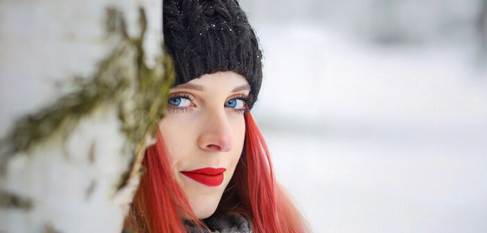 woman with red hair and red lipstick against a snowy backdrop