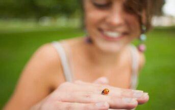 curious young woman holding a ladybird