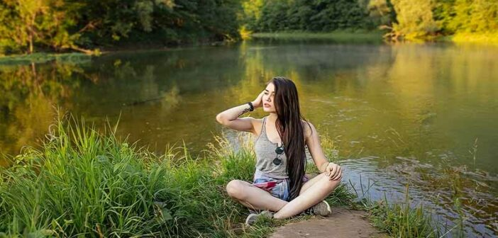 young woman sitting by lake - illustrating a fulfilling life
