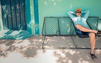 lazy man sitting outside house