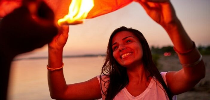 young woman feeling joy as she releases a lantern into the sky