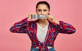 woman putting tape across her mouth to illustrate keeping your mouth shut