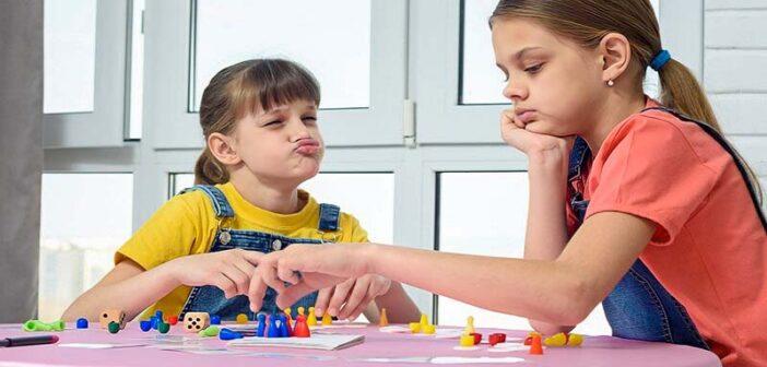 sore loser child making face at sibling