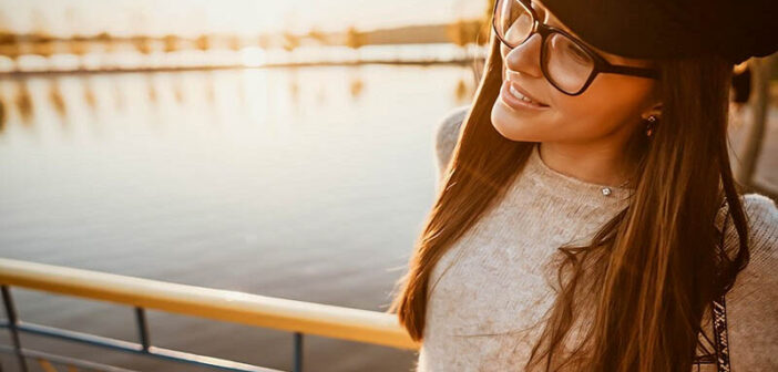 young smiling woman standing by river after changing her life