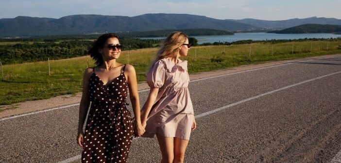two friends who trust each other walking alone a coastal road